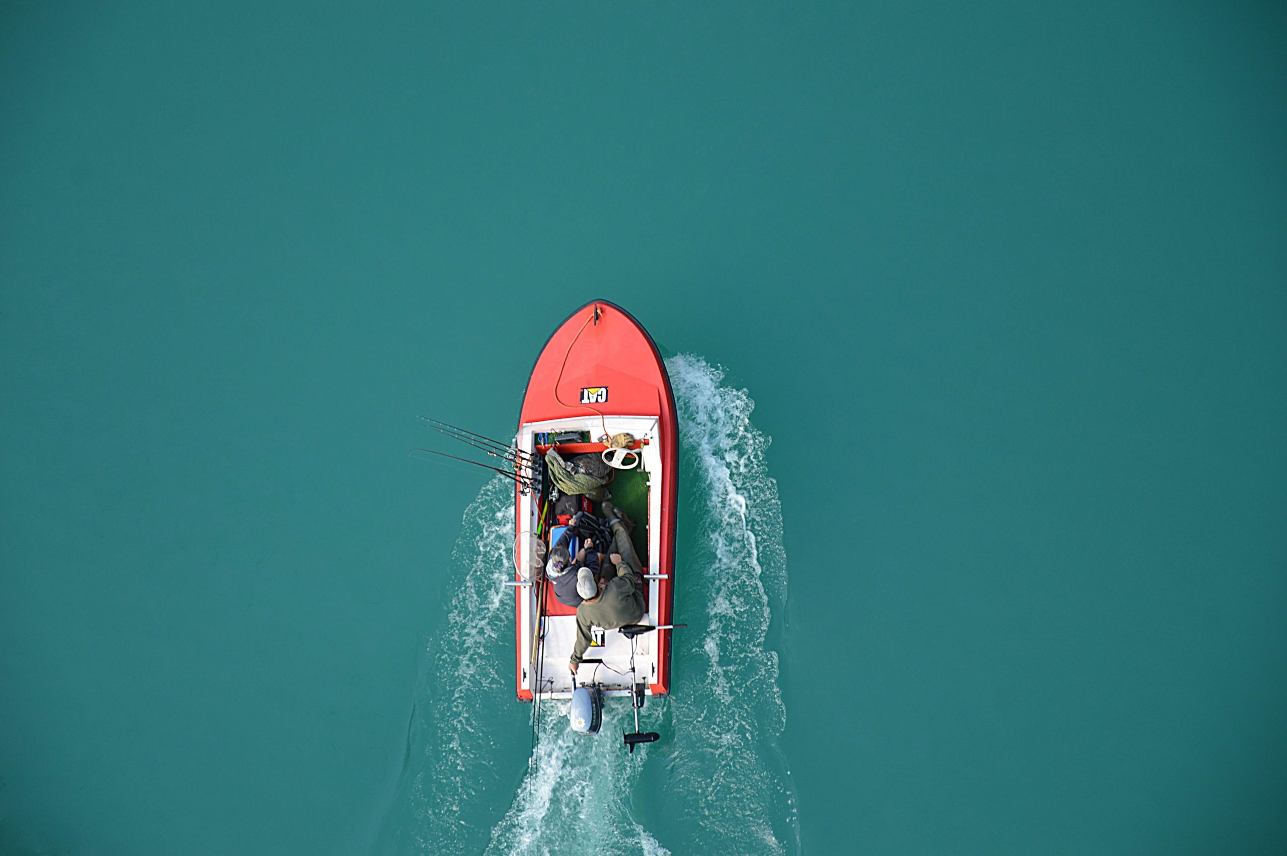 Fishermen on boat with fishing rods hanging off side