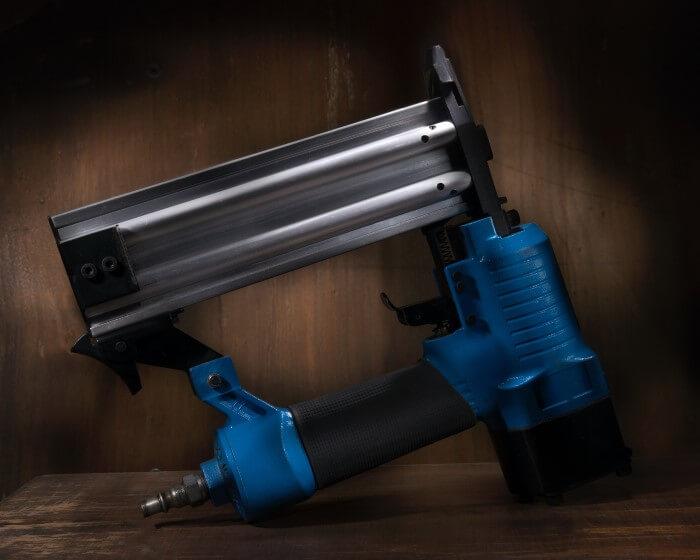 nail gun resting on wood table