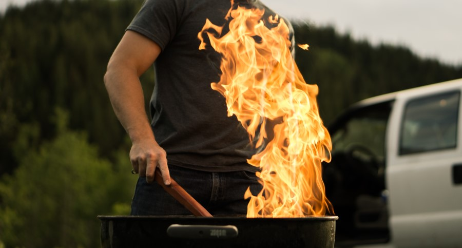 person grilling with large flame flare up in front of truck